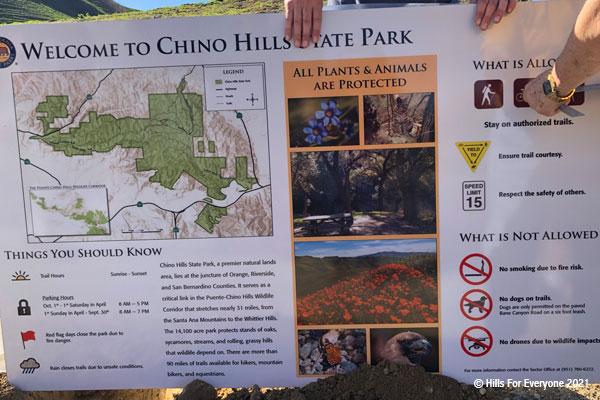 A Welcome to Chino Hills State Park is held by two hands and another set of hands measures the distance from the edge of the sign.
