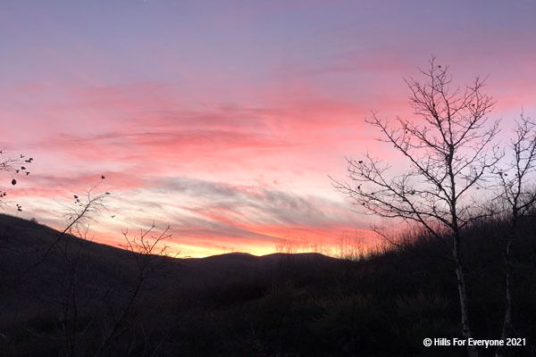In the foreground some hills and vegetation with a tree silhouetted against a multi-colored sunset of yellows, orange, pink, and purple with scattered pink clouds.