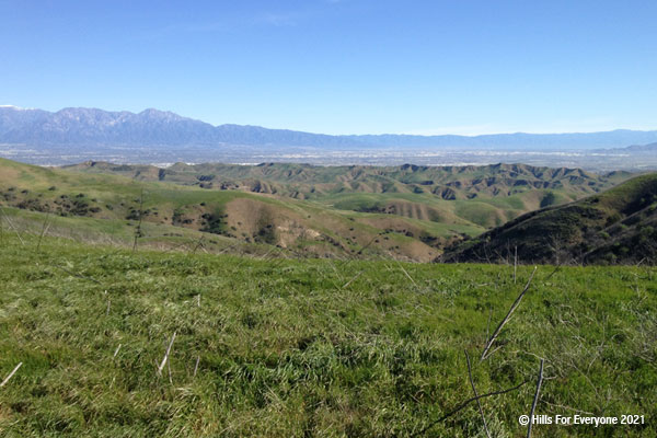 A view of flat green space in the foreground with many rows of ridgelines and hills to a plain in the distance with grey mountains and a medium blue sky above