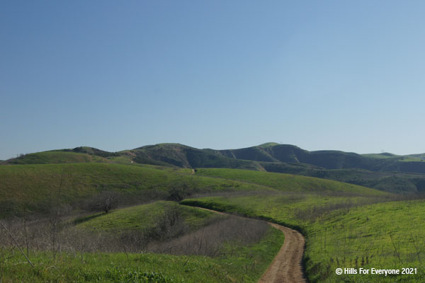 A dirt trail in the center goes left and is surrounded by green grassy hillsides with rolling hills in the distance and a blue sky above.