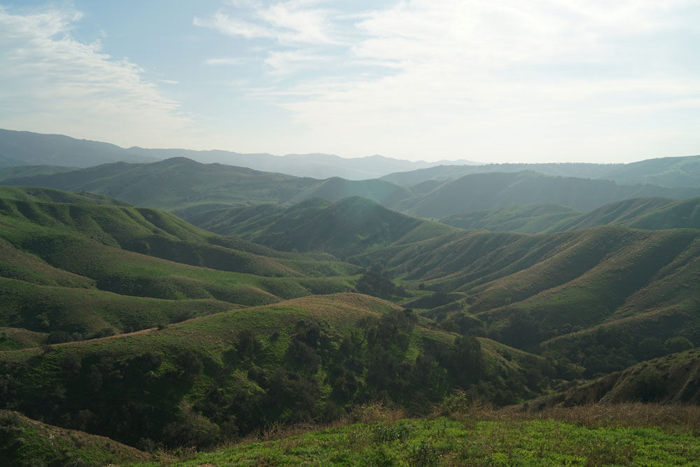 A view of multiple canyons and ridgelines in green and slightly brown shades with a hazy sky with medium blues and dusty white wispy clouds.